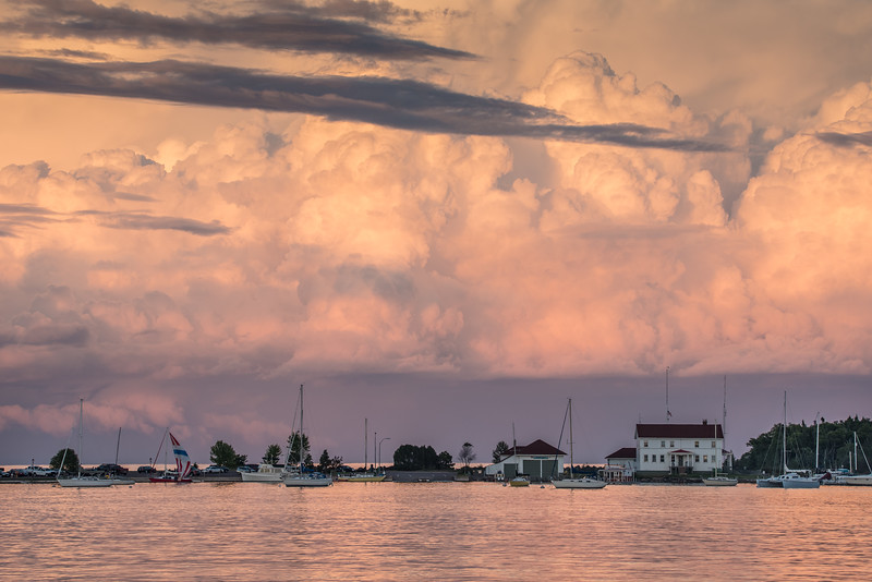 "TUESDAY, AUGUST 7, 2015<br /> <br /> GRAND MARAIS 8603<br /> <br /> ""Storm Cloud Sunset, Grand Marais Harbor""<br /> <br /> Wow, yesterday was an amazing day for photography!  For most of the day we had the most incredible thunderstorm cloud formations moving across the area.  My friend Roger and I spent most of the afternoon and evening chasing the storm clouds to photograph them.  Our day ended along the harbor in Grand Marais, where the last of the storm clouds was moving southeast across Lake Superior.  The scene was a surreal one as we drove from the Gunflint Trail down the hill and into town.  The storm cloud formation was right over Artist's Point, the coast guard station and the lighthouse.  Lots of people were out along the shoreline of the harbor enjoying the view of the retreating clouds.  It was the perfect end to an adventurous day of photography!<br /> <br /> Camera: Nikon D750<br /> Lens: Tamron SP 150-600mm<br /> Focal length: 150mm<br /> Shutter speed: 1/200<br /> Aperture: f/11<br /> ISO: 400"
