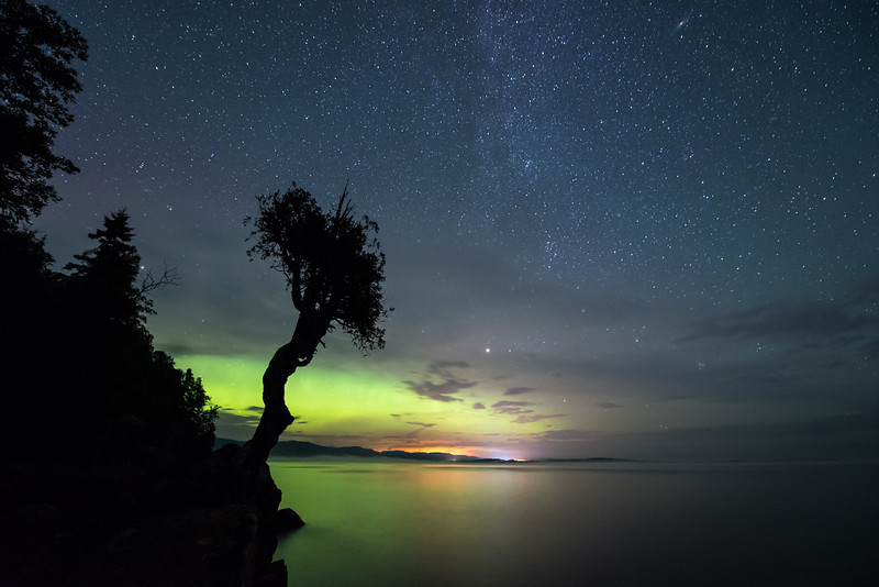 """SUNDAY, AUGUST 9, 2015<br /> <br /> SPIRIT TREE 8315<br /> <br /> """"Rendezvous Days Aurora""""<br /> <br /> As I mentioned in my post yesterday, it is the annual Grand Portage Rendezvous Days Celebration this weekend.  We have a big pow-wow that goes on all weekend and Grand Portage National Monument has their big reenactment going on as well.  I don't normally visit the Spirit Tree on Rendezvous weekend but this year I have company and wanted to show the tree to them.  Since the space weather forecast was calling for a chance of northern lights I decided that we should visit the tree late at night to watch the crescent moon rise and wait for the northern lights to show up.  There were indeed some lights, but just a soft green glow on the horizon.  It was a very pretty night with the stars, clouds, northern lights, moonlight and the occasional Perseid meteor streaking across the sky.<br /> <br /> Camera: Nikon D750<br /> Lens: Nikon 14-24mm f/2.8<br /> Focal length: 14mm<br /> Shutter speed: 30 seconds<br /> Aperture: f/2.8<br /> ISO: 3200"""