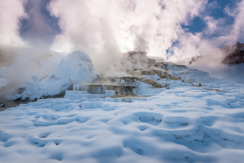 """FRIDAY, DECEMBER 11, 2015<br /> <br /> WYOMING 5040<br /> <br /> """"Mammoth Steam""""<br /> <br /> Our last stop before leaving Yellowstone was a visit to Mammoth Hot Springs.  This is a fascinating area to see at any time of year but especially so in winter.  The hot geothermal features clashing with the cold air and snowy landscape make for quite a unique scene.<br /> <br /> Camera: Nikon D750<br /> Lens: Nikon 16-35mm f/4<br /> Focal length: 16mm<br /> Shutter speed: 1/100<br /> Aperture: f/16<br /> ISO: 200"""