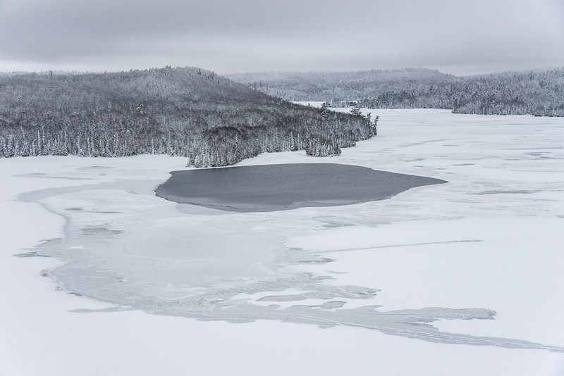 "THURSDAY, DECEMBER 24, 2015<br /> <br /> LAKES 5544<br /> <br /> ""Slow Freeze""<br /> <br /> Here is another photo of Hungry Jack Lake from earlier this week.  Also taken from Honeymoon Bluff, this time looking west across the lake (the last photo I posted was looking north).  Typically the lake would be completely frozen by now but as you can see there is still a bit of open water.  I really liked the little patch of open water for this photo, as well as the patterns in the ice.  I would have loved to see this view on a nice blue sky day but it was very beautiful even on such a gray day.<br /> <br /> Camera: Nikon D750<br /> Lens: Nikon 24-120mm f/4<br /> Focal length: 82mm<br /> Shutter speed: 1/640<br /> Aperture: f/11<br /> ISO: 800"