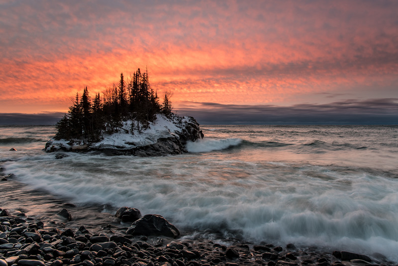 """WEDNESDAY, DECEMBER 30, 2015<br /> <br /> SUPERIOR WINTER 5626<br /> <br /> """"Mild Winter Morning at the Rock Island""""<br /> <br /> I think this might be a """"bad"""" winter for ice on the Lake Superior shoreline.  So far this year it hasn't been cold enough for any significant ice to start forming. I stopped by here yesterday morning and the sky was pretty but if it weren't for the little bit of snow and ice on the island, you'd never know this was a winter shot.  There is still a lot of winter left, though, so there might still be some hope for decent ice along the shoreline.  Time will tell!<br /> <br /> Camera: Nikon D750<br /> Lens: Nikon 24-120mm f/4<br /> Focal length: 24mm<br /> Shutter speed: 0.4 seconds<br /> Aperture: f/11<br /> ISO: 100"""
