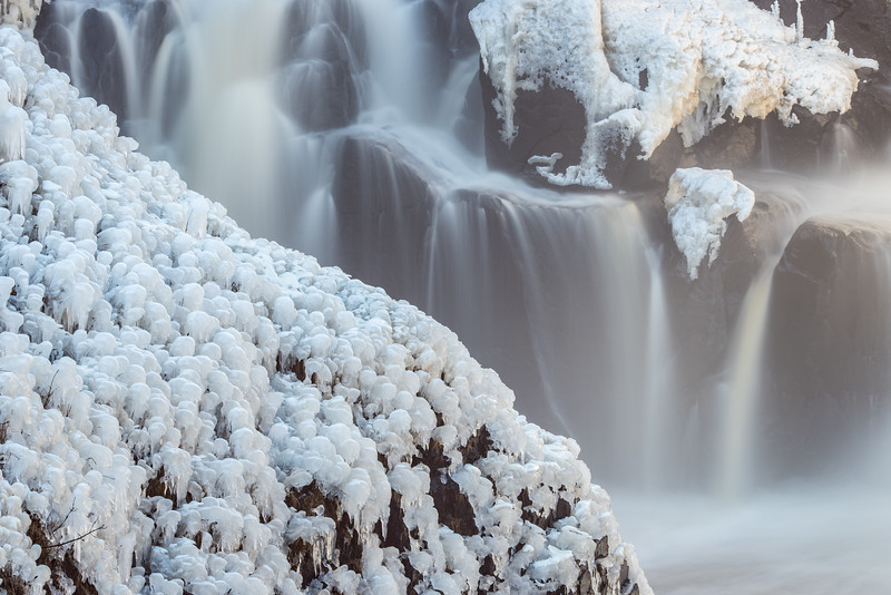 """THURSDAY, DECEMBER 16, 2015<br /> <br /> PIGEON RIVER 5300<br /> <br /> """"Early Ice at High Falls""""<br /> <br /> We haven't had much of a winter yet this year.  After getting an early fix of winter during our visit to Yellowstone, we returned to spring-like weather in Minnesota.  The temperatures have been in the low to mid 40's and we've been getting rain, not snow.  Until today, that is.  <br /> <br /> Today we are finally getting some snow, even if it is of the wet and sloppy variety.  Still, it is snow and things are turning white.  Even though it hasn't been very cold, it has been cold enough for a little ice to start forming on High Falls of the Pigeon River.  This waterfall is such a fascinating one to photograph.  It has so much variety in it from one day to the next.  <br /> <br /> Today's photo was taken about a week ago and shows just the bottom left portion of the falls.  The river level was high enough and the air cold enough that the mist from the falls was freezing on the sides of the gorge.  It is one of my favorite times of year to make images of the waterfall, as the mixture of open water and ice makes for some fun photography!<br /> <br /> Camera: Nikon D750<br /> Lens: Tamron SP 150-600mm<br /> Focal length: 210mm<br /> Shutter speed: 5 seconds<br /> Aperture: f/16<br /> ISO: 100"""