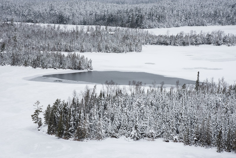 """THURSDAY, DECEMBER 24, 2015<br /> <br /> LAKES 5527<br /> <br /> """"Winter Wonderland - Hungry Jack Lake""""<br /> <br /> The other day I took a drive up the Gunflint Trail to see how winter was progressing inland from Lake Superior.  As you already know from my previous posts, winter along the Superior shoreline has been very slow to arrive this year.  Instead of snow we've been getting rain.  In fact, it rained again all day yesterday.  Inland, however, it has been snowing more than raining thanks to cooler temperatures away from Lake Superior.  <br /> <br /> We had a big storm a little over a week ago that left quite a bit of snow along the Gunflint Trail.  Amazingly, a week after the storm most of the trees were still coated in a thick blanket of snow.  Usually our winter storms are trailed by high winds and indeed we did have a lot of wind along the Superior shoreline.  Either there wasn't as much wind inland or the snow was so wet that it clung to the trees despite the wind.  <br /> <br /> At any rate, my drive along the Gunflint two days ago was like driving through a classic winter postcard scene.  Everything was white, everywhere you looked!  This photo was taken from the Honeymoon Bluff trail overlooking Hungry Jack Lake.  I was surprised to see that the lake still had several patches of open water.  Usually the lakes would be completely iced over by now.  Another testament to the mild winter we're having thus far.<br /> <br /> Camera: Nikon D750<br /> Lens: Nikon 24-120mm f/4<br /> Focal length: 75mm<br /> Shutter speed: 1/250<br /> Aperture: f/16<br /> ISO: 800"""