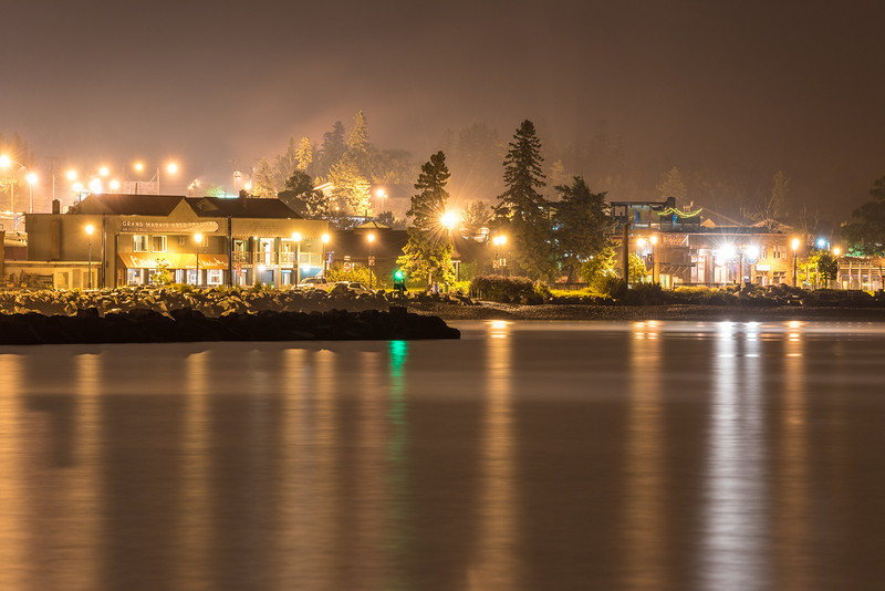 "TUESDAY, JULY 7, 2015<br /> <br /> GRAND MARAIS 6901<br /> <br /> ""Foggy Night in Grand Marais, MN""<br /> <br /> The last hour of Sunday, July 5th went out with a bang.  All day long I had been watching the forecast as it predicted heavy rain and powerful thunderstorms for the coming night.  Sure enough, at 10 PM the weather radar showed an intense line of storms heading towards Lake Superior all along the Minnesota north shore from Duluth to Grand Portage. I decided to make a quick run to Grand Marais to try and photograph the lightning over the harbor from the safety of the covered picnic shelter at the municipal campground.  <br /> <br /> For the entire 45 minute drive from our house to Grand Marais I witnessed countless amazing lightning flashes, torrential rain downpours and thick fog.  By the time I got to Grand Marais 90% of the storm had passed.  The lightning was basically done, and all that was left was an intermittent fog over the harbor.  The air was very still and quiet the rest of the night. I was disappointed to have missed the lightning, but I really enjoyed watching and photographing the changing fog conditions over the harbor.  This photo was made at 12:03 AM the morning of July 6th. It shows the Harbor Inn building on the left and the Gunflint Tavern on the right with the Johnson Heritage Post in between.  I may not have gotten the lightning shots I was hoping for, but I really like this image too!<br /> <br /> Camera: Nikon D750<br /> Lens: Tamron SP 150-600mm<br /> Focal length: 350mm<br /> Shutter speed: 8 seconds<br /> Aperture: f/8<br /> ISO: 400"