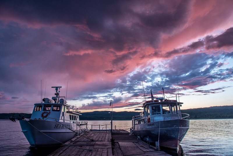 "SATURDAY, JULY 25, 2015<br /> <br /> SUPERIOR BOATS 7341<br /> <br /> ""A slightly surreal sunset over the Isle Royale Boats""<br /> <br /> It was a bit of a surreal sunset last night!  Rarely do we see sunsets that light up the entire sky with color, but last night was one of those rare times when exactly that happens.  There were clouds all over in every direction of the sky and every one of them was lit up with some amazing color.  We were just getting ready to start watching a movie when I looked out our dining room window and noticed the sky colors getting really intense.  At first I walked around our yard snapping pictures of the clouds but I couldn't get enough of the sky in my shots to catch all the color.  So, I hopped in the car and drove over to Hat Point Marina where there is a more open view.  By the time I got over there the most intense color had faded but the afterglow was beautiful too.  That was when the surreal part kicked in.  The color tone had changed enough in the afterglow that I couldn't believe what I was seeing.  I've seen colors like this before but rarely so prominently throughout the sky.  I decided to frame a shot of the sunset with the ferries of the Grand Portage - Isle Royale Transportation Line in the foreground. <br /> <br /> The Grand Portage - Isle Royale Transportation Line provides passenger service from Grand Portage, MN to Isle Royale National Park in Michigan.  They run two ferries, the Sea Hunter III (pictured on the left) which runs day trips to Windigo, and the Voyageur II (on the right) which circles the entire island and makes stops at various points along the way.  The Voyageur II spends the night at Rock Harbor, making the round-trip of Isle Royale a two-day affair.  If you'd like to find out more information about making a trip to Isle Royale via one of these ferries, you can check out Grand Portage - Isle Royale Transportation Line's website at <a href=""http://www.isleroyaleboats.com"">http://www.isleroyaleboats.com</a>.<br /> <br /> Camera: Nikon D750<br /> Lens: Nikon 24-120mm f/4<br /> Focal length: 24mm<br /> Shutter speed: 1/30<br /> Aperture: f/8<br /> ISO: 200"