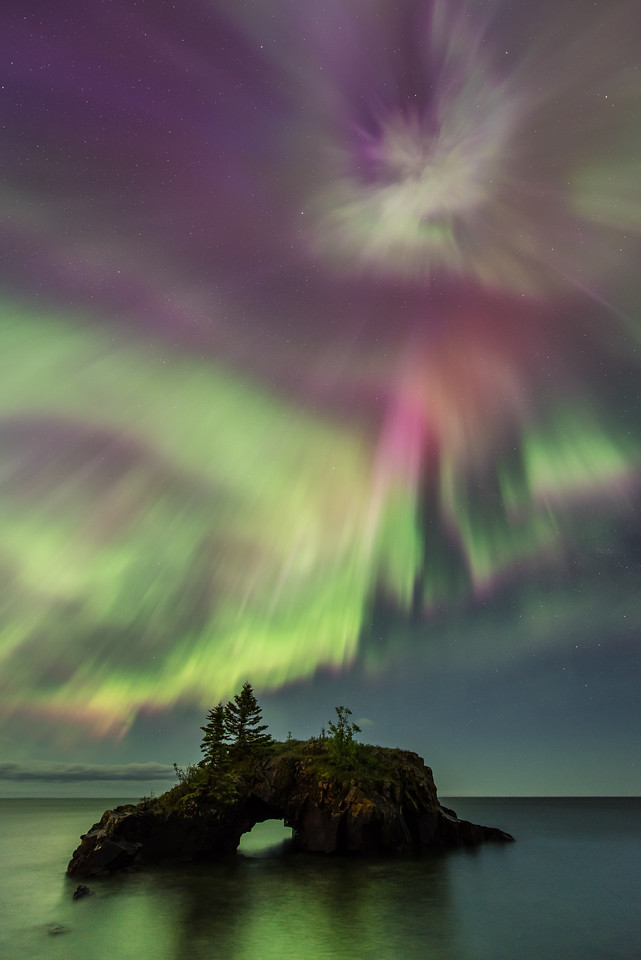 "TUESDAY, JUNE 23, 2015<br /> <br /> AURORA 6388<br /> <br /> ""Solar Storm Explosion!""<br /> <br /> This photo was made at 12:30 AM last night at Hollow Rock in Grand Portage, MN.  It was the most intense moment of colors in the aurora that I witnessed last night.  For only a minute or two there was this brief explosion of purples, pinks and reds over Hollow Rock.  The rest of the time the lights were a predominantly green color with some purples here and there.  The reds and pinks in this brief explosion were spectacular and the highlight of an unforgettable night of aurora photography!<br /> <br /> Camera: Nikon D750<br /> Lens: Nikon 14-24mm f/2.8<br /> Focal length: 14mm<br /> Shutter speed: 10 seconds<br /> Aperture: f/2.8<br /> ISO: 1000"
