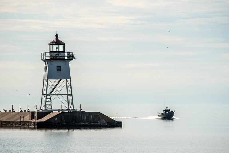 "SATURDAY, JUNE 20, 2015<br /> <br /> GRAND MARAIS 5844<br /> <br /> ""The Daily Return""<br /> <br /> Earlier this week, Harley Toftey's boat returns to the Grand Marais Harbor and Dockside Fish Market with the day's catch.  I was passing Five Mile Rock on my way to Grand Marais and saw a boat traveling out on the lake.  I took a picture of that boat with my telephoto lens and realized it was Harley's boat.  Knowing that he was likely heading for the harbor, I drove straight to the municipal campground and waited on the shoreline for the boat to show up around the lighthouse.  I only had to wait a few minutes before I saw him coming.<br /> <br /> Camera: Nikon D750<br /> Lens: Tamron SP 150-600mm<br /> Focal length: 460mm<br /> Shutter speed: 1/1250<br /> Aperture: f/11<br /> ISO: 200"