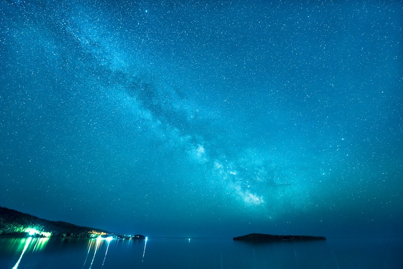 """THURSDAY, JUNE 11, 2015<br /> <br /> MILKY WAY 5506<br /> <br /> """"Grand Portage Night Sky""""<br /> <br /> When the weather allows (which has been a rarity in recent days), our views of the night sky along the north shore of Lake Superior continue to impress!  Here is a recent image that I captured just 1/4 mile down the road from our house.  The Milky Way over Pete's Island and Hat Point in Grand Portage Bay.  The light that you see on the water between the point and the island is from the bell buoy which marks a reef just outside the bay.<br /> <br /> Camera: Nikon D750<br /> Lens: Nikon 14-24mm f/2.8<br /> Focal length: 14mm<br /> Shutter speed: 25 seconds<br /> Aperture: f/2.8<br /> ISO: 6400"""