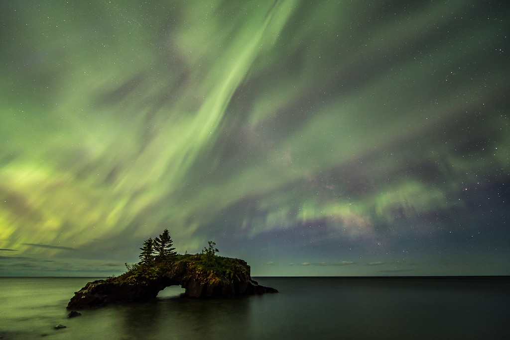 "TUESDAY, JUNE 23, 2015<br /> <br /> AURORA 6151<br /> <br /> ""Hollow Rock, the Aurora Borealis and the Milky Way""<br /> <br /> Here's another image of Hollow Rock from last night's aurora storm.  I still cannot believe how active the aurora was over Lake Superior!  Normally we don't see the northern lights over the lake that much here on the north shore because when we are looking out at the lake we are looking south.  But last night the majority of the activity was out over the lake.  I love that the Milky Way was still showing in this photo even though the aurora lights were so strong.<br /> <br /> Camera: Nikon D750<br /> Lens: Nikon 14-24mm f/2.8<br /> Focal length: 14mm<br /> Shutter speed: 15 seconds<br /> Aperture: f/2.8<br /> ISO: 1250"