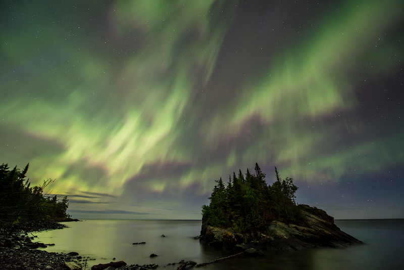 """TUESDAY, JUNE 23, 2015<br /> <br /> AURORA 6130<br /> <br /> """"Summer Solstice Solar Storm""""<br /> <br /> The summer solstice solar storm arrives!  What an insane night!  For the first few hours of darkness, the sky was filled with some of the most incredible northern lights that I've ever seen in northeast Minnesota.  Space weather forecasts were originally calling for this storm to arrive the previous night and indeed there was a subtle amount of aurora activity but the main impact of the storm was yet to come.  Well, last night it arrived with a vengeance!  I left the house just as it was getting dark and had planned on driving about 20 miles inland to one of my favorite lakes.  However, as I drove down Highway 61 I could see the lights dancing in the southern sky over Lake Superior!  So, I changed my plan and stopped by Horseshoe Bay in Hovland.  There is a small island just off the shoreline in this location and it was the perfect place for my first shooting location of the evening.<br /> <br /> Camera: Nikon D750<br /> Lens: Nikon 14-24mm f/2.8<br /> Focal length: 14mm<br /> Shutter speed: 20 seconds<br /> Aperture: f/2.8<br /> ISO: 1250"""