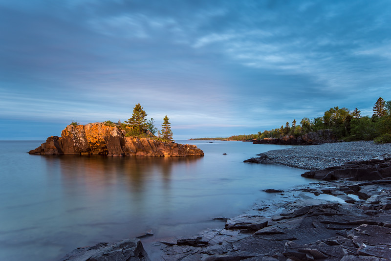 """MONDAY, JUNE 29, 2015<br /> <br /> SUPERIOR SUMMER 5762<br /> <br /> """"First Light on The Rock""""<br /> <br /> Hollow Rock is simply beautiful as the first light of a summer day washes over it.  I love the really calm water that is common this time of year.  It makes for wonderful reflections on these calm mornings.  I sure do feel fortunate to be surrounded by so many wonderful things to photograph!<br /> <br /> Camera: Nikon D750<br /> Lens: Nikon 16-35mm f/4<br /> Focal length: 23mm<br /> Shutter speed: 20 seconds<br /> Aperture: f/8<br /> ISO: 100"""