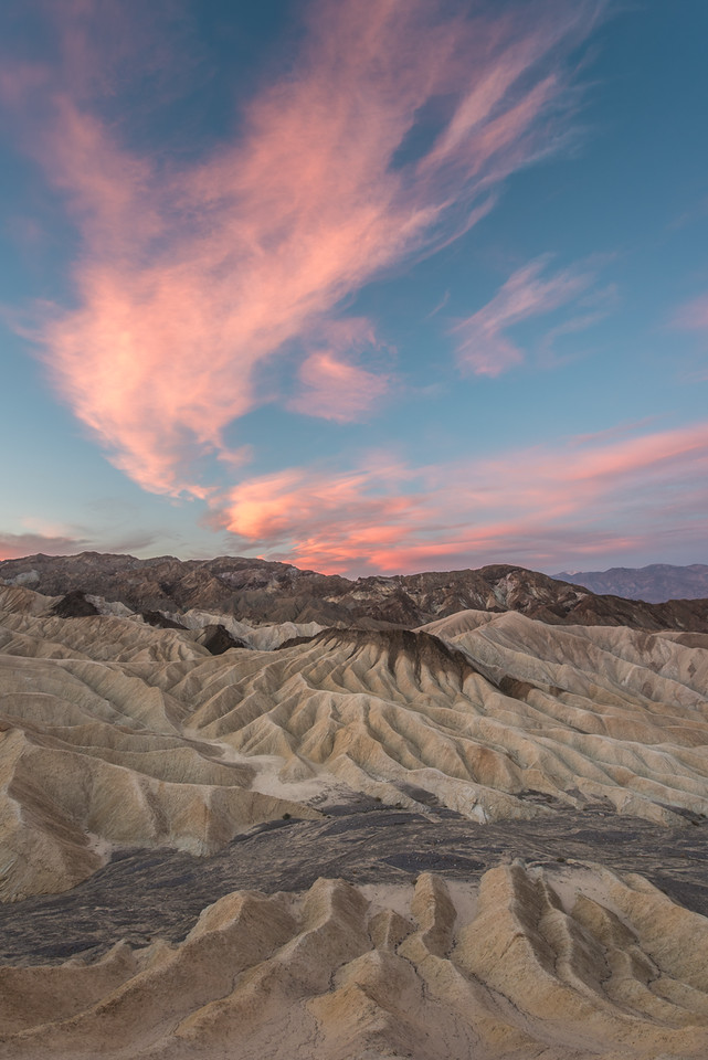 "FRIDAY, MARCH 27, 2015<br /> <br /> CALIFORNIA 1729<br /> <br /> ""Sunrise at Zabriskie Point""<br /> <br /> Probably the biggest surprise of our trip was being able to photograph Zabriskie Point at sunrise.  We had figured that we would have to save this location for a future trip. We had it on good authority that the park service had completely closed the area while they made repairs to the walkway.  Indeed, Zabriskie Point had been completely closed down.  However, they had finished the work well ahead of schedule and the point had re-opened more than a month earlier than they had planned!  This changed our itinerary immediately and we planned on doing sunrise the next day at the the point.  We sure are glad it was open because we had an AMAZING sunrise!  The view shown in this photo is actually looking sort of west-southwest, the opposite direction from which the sun was rising.  It was one of those mornings, though, where the clouds all throughout the sky glowed with this rich color from the rising sun.  And we sure had some beautiful clouds that morning!<br /> <br /> Camera: Nikon D750<br /> Lens: Nikon 14-24mm f/2.8<br /> Focal length: 14mm<br /> Shutter speed: 0.4 seconds<br /> Aperture: f/16<br /> ISO: 200"