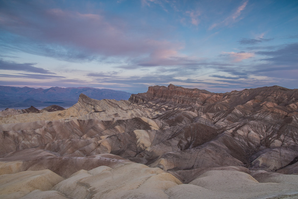 "SUNDAY, MARCH 29, 2015<br /> <br /> CALIFORNIA 1739<br /> <br /> ""Zabriskie's morning palette""<br /> <br /> I'd like to share one more image from Zabriskie Point in Death Valley.  Our friend that gave us advice on where to go in the park said that Zabriskie was his favorite location and we can definitely see why!  It is, arguably, the most photogenic area of the park.  It's probably safe to say that it is the most photographed area in the park as well.  There certainly were plenty of other photographers there sharing the scene with us!  I made this photograph a while after the initial burst of morning color lit up the clouds.  The sun had illuminated the clouds with vibrant pinks and reds, then went behind a layer of clouds which really softened the light.  That's when I made this photo.  The clouds still had color in them, but it was more subdued.  I really like the softer quality of the light in this photo.  It's one of my favorite photographs from our morning at Zabriskie Point.<br /> <br /> Camera: Nikon D750<br /> Lens: Nikon 24-120mm f/4<br /> Focal length: 24mm<br /> Shutter speed: 1/6<br /> Aperture: f/14<br /> ISO: 200"
