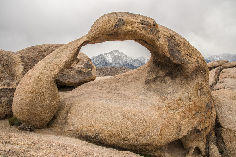 "MONDAY, MARCH 30, 2015<br /> <br /> CALIFORNIA 1945<br /> <br /> ""Mobius Arch and the Eastern Sierras""<br /> <br /> After leaving Death Valley we headed north.  Our next layover was to be Mono Lake in Lee Vining, California.  Along the way we had a couple of ideas for places to check out.  We ended up going with the Alabama Hills just outside the town of Lone Pine.  The Alabama Hills are famous for western movies being filmed there.  In fact, according to literature at the nearby forest service visitor center, over 200 movies have been filmed in the area.  It was a fascinating area with many interesting rock formations.  The background was  magnificent, a stunning view of the Eastern Sierra mountains including Mount Whitney, the tallest peak in the lower 48 with an elevation of 14,505 feet.  We spent a couple of hours in the Alabama Hills which included a hike to the famous Mobius Arch, seen in this photo.  The sky wasn't the best during our visit here, but we still really enjoyed all the beautiful scenery.  <br /> <br /> NOTE: Mount Whitney is NOT visible in this photo, it is behind the right arm of the arch.<br /> <br /> Camera: Nikon D750<br /> Lens: Nikon 24-120mm f/4<br /> Focal length: 24mm<br /> Shutter speed: 1/160<br /> Aperture: f/16<br /> ISO: 400"