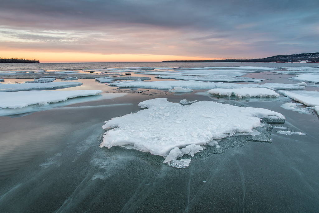 "THURSDAY, MARCH 12, 2015<br /> <br /> SUPERIOR SPRING 1242<br /> <br /> ""The Last Ice""<br /> <br /> Well, I think this is it. The last of the floating ice in Grand Portage Bay for this year.  We have had a major meltdown over the last few days and this ice that I photographed on Tuesday morning is pretty much gone now.  I was intrigued by the look of the ice in the foreground that was just under the surface of the water.  I loved all the lines in the ice and the translucence of it.  You can also see how shallow the water is in this part of the bay.  If you look at the left side of the photo, you can see the sand ripples on the lake bottom.  There is only about one foot of water depth here.  So, some of these larger chunks of ice were actually sitting on the bottom of the lake.<br /> <br /> Camera: Nikon D750<br /> Lens: Nikon 24-120mm f/4<br /> Focal length: 24mm<br /> Shutter speed: 1/4<br /> Aperture: f/16<br /> ISO: 200"