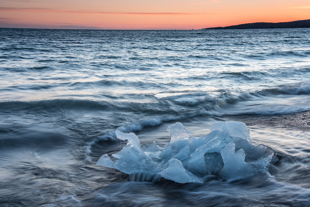 "SUNDAY, MARCH 8, 2015<br /> <br /> SUPERIOR SPRING 0997<br /> <br /> ""The Last Iceberg""<br /> <br /> The last remaining iceberg on a shoreline that had ice as far as the eye could see just a week previously.  I was hoping for a little more sky interest on this evening but the sky was almost completely devoid of clouds.  In the end that didn't matter as I found one of the most uniquely shaped icebergs that I've ever seen so I made that the prominent feature of this photo.  It was fun photographing the waves washing over this chunk of ice.  Every photo that I made looked completely different from the last with the ever-changing patterns of the waves.<br /> <br /> Camera: Nikon D750<br /> Lens: Nikon 24-120mm f/4<br /> Focal length: 48mm<br /> Shutter speed: 1/3<br /> Aperture: f/16<br /> ISO: 200"