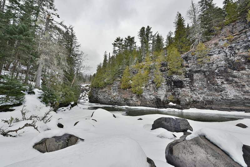 "SATURDAY, MARCH 14, 2015<br /> <br /> PIGEON RIVER 1388<br /> <br /> ""Pigeon River Gorge""<br /> <br /> The past couple of days I've noticed a lot of otter tracks in the snow in the Pigeon River gorge just below High Falls.  So, this morning I took a walk into the gorge to see if maybe the otters were out.  Unfortunately I never saw them.  It was fun seeing their tracks though and the gorge is always beautiful.  While I was there I made this HDR (high dynamic range) image looking upstream in the gorge.  High Falls is just around the corner to the right as you're looking upstream.  I don't normally like to do HDR images as I don't care for the look of them, but this scene called for it so I decided to experiment with one.<br /> <br /> Camera: Nikon D750<br /> Lens: Nikon 14-24mm f/2.8<br /> Focal length: 14mm<br /> Shutter speed: 1/320<br /> Aperture: f/8<br /> ISO: 400"