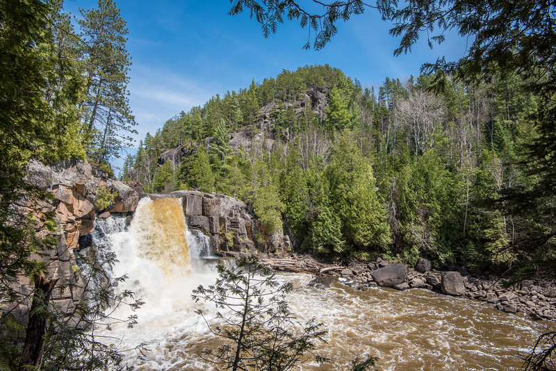 """THURSDAY, MAY 7, 2015<br /> <br /> ONTARIO 4949<br /> <br /> """"The Reward""""<br /> <br /> May 7, 2015 - Yesterday I hiked to a waterfall that I've heard about now and then over the years but had never been to.  It wasn't an overly long hike (less than a mile), but it was pretty brutal as there is no trail and you have to cross some fairly rugged terrain getting there.  The amount of brush and fallen trees made for a challenge.  I was glad I was doing the hike in the spring before the trees leafed out, as I could somewhat see the best route ahead of me.  Once the leaves are out it would be much harder to find the path of least resistance.  <br /> <br /> By the time I got back to the truck I was a sweaty mess, covered with scratches up and down my arms from pushing my way through the brush.  I had spruce needles everywhere... in my pockets, in my shoes, down my shirt.  I had a nice big rip in the right sleeve of my shirt.  Oh, and I found about a dozen wood ticks on me.  The hike was worth all that, though, as the waterfall was very impressive and certainly in a beautiful location with the big hill providing a dramatic backdrop to the falls.  Oh, in case you're wondering... this is on the Arrow River in Ontario :-)<br /> <br /> Camera: Nikon D750<br /> Lens: Nikon 16-35mm f/4<br /> Focal length: 16mm<br /> Shutter speed: 1/160<br /> Aperture: f/16<br /> ISO: 200"""
