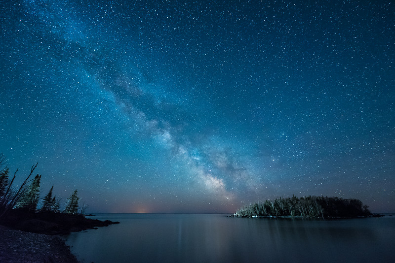 """TUESDAY, MAY 19, 2015<br /> <br /> MILKY WAY 4297<br /> <br /> """"Milky Way and Pancake Island""""<br /> <br /> The new moon was just the other night.  It is the time each month when our night sky is the darkest and the best time for photographing the Milky Way.  Unfortunately, our skies have been mostly cloudy lately and now I'm coming a bit under the weather so it looks like I may not get out for any night shooting in the immediate future.  So, here's a photo from last month's new moon that I've been saving for a time such as this!  <br /> <br /> This photo was made on April 18th, 2015 at 3:30 in the morning over one of the islands along the Lake Superior shoreline in Grand Portage, MN.  The light that you see illuminating the left end of the island is from a yard light from a nearby home just around the point on the left side of the photo.  Normally I don't like artificial light at all in such a photo, but in this case part of me doesn't mind because it almost looks as though it is the Milky Way itself that is casting the light on the island.  This photo was made with a Nikon 14-24mm f2.8 lens, exposure length was 25 seconds at f/2.8 with an ISO of 6400.<br /> <br /> Camera: Nikon D750<br /> Lens: Nikon 14-24mm f/2.8<br /> Focal length: 14mm<br /> Shutter speed: 25 seconds<br /> Aperture: f/2.8<br /> ISO: 6400"""