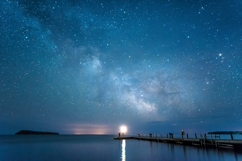 """FRIDAY, MAY 1, 2015<br /> <br /> MILKY WAY 4452<br /> <br /> """"See the Milky Way at Grand Portage National Monument!""""<br /> <br /> One of the best (and easiest) places to view the Milky Way in Grand Portage is to walk out to the end of the dock at Grand Portage National Monument and gaze south across Lake Superior.  It also makes for an interesting self-portrait by setting the timer on your camera and walking out to the end of the dock to put yourself in the picture (as I did here).  True, there is a blinking navigation light on the end of the dock, but it barely interferes with the view of the stars above as it only blinks for a moment every few seconds and is not an obnoxious light.  In this photo there is a cloud bank low on the horizon which amplifies light pollution from cities in the upper peninsula of Michigan, far across the wide expanse of Lake Superior.<br /> <br /> Camera: Nikon D750<br /> Lens: Nikon 14-24mm f/2.8<br /> Focal length: 24mm<br /> Shutter speed: 25 seconds<br /> Aperture: f/2.8<br /> ISO: 6400"""