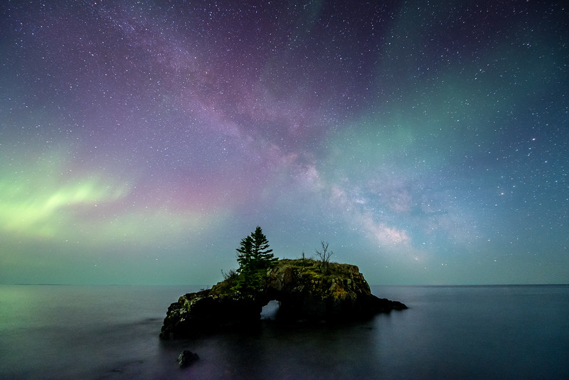 """THURSDAY, MAY 14, 2015<br /> <br /> AURORA 5224<br /> <br /> """"Celestial Fantasy""""<br /> <br /> It's not very often when the conditions align so you can get a photograph such as this!  Only one other time have I been able to capture the Aurora Borealis over Hollow Rock, and that was on a partly cloudy night.  This time, in the early morning hours of May 13th, 2015 I was able to capture not only the northern lights but also the Milky Way over Hollow Rock!  We experienced quite an aurora storm, strong enough that the lights were visible to the south over Lake Superior.  And, not only were the common green colors of the aurora visible, there were some shades of purple as well (which also made part of the Milky Way appear purple).  As you can imagine, I was pretty excited to not only witness such beauty but to be able to capture it on camera as well.  It literally was a fantasy come true.  My own """"Celestial Fantasy"""", if you will :-)<br /> <br /> Camera: Nikon D750<br /> Lens: Nikon 14-24mm f/2.8<br /> Focal length: 14mm<br /> Shutter speed: 25 seconds<br /> Aperture: f/2.8<br /> ISO: 3200"""