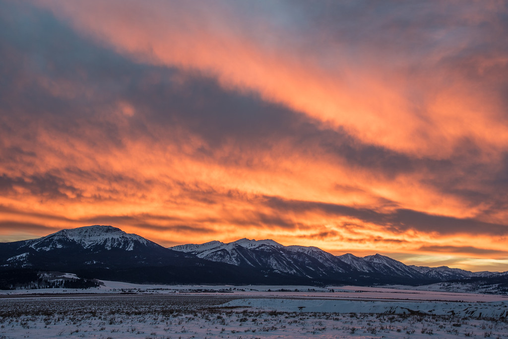 "WEDNESDAY, NOVEMBER 25, 2015<br /> <br /> IDAHO 4524<br /> <br /> ""Fiery Sunset over the Continental Divide""<br /> <br /> The other day after watching the moon rise over the Madison Range, we continued driving south back towards Highway 20 and West Yellowstone.  It had been a very gray afternoon with relatively thick cloud cover.  As sunset approached, however, there must have been a break in the clouds to the west.  We driving along when Jessica said ""Ooooh, the sky is lighting up!""  Just moments later the sky was on fire with the reflected light from the sun setting behind the mountains.  We looked for the next available spot to pull over and enjoyed this amazing sunset from the side of the highway.  The mountains shown include Sawtell Peak, Mt. Jefferson and Nemesis Mountain.  The Continental Divide is in between Sawtell Peak in Idaho and Nemesis Mountain in Montana.<br /> <br /> Camera: Nikon D750<br /> Lens: Nikon 24-120mm f/4<br /> Focal length: 48mm<br /> Shutter speed: 1/25<br /> Aperture: f/11<br /> ISO: 200"