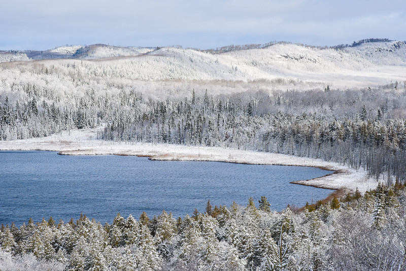 "SATURDAY, NOVEMBER 14, 2015<br /> <br /> LAKES 4266<br /> <br /> ""First Snow at Teal Lake""<br /> <br /> Yesterday morning we woke up to a beautiful world of white!  It was the first measurable snowfall of the season near the Lake Superior shoreline in Grand Portage.  We had an inch or two of snow fall near the lake, with 3 to 4 inches or so further inland.  I stopped a few places on my way to work to make some pictures of the fresh snow, including this Highway 61 road-side stop that gives a view of Teal Lake just a few miles south of the Canadian border.  I don't recall ever seeing so much snow blanketing the trees while the lake was still a beautiful blue with no ice yet formed on its surface.  Most of this snow has already melted but hopefully we will have more soon!<br /> <br /> Camera: Nikon D750<br /> Lens: Nikon 24-120mm f/4<br /> Focal length: 120mm<br /> Shutter speed: 1/500<br /> Aperture: f/16<br /> ISO: 800"