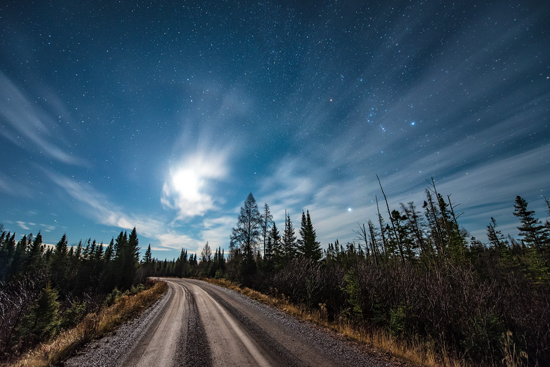 """FRIDAY, NOVEMBER 6, 2015<br /> <br /> MOONLIGHT 4157<br /> <br /> """"Back Roads Moonlight, Superior National Forest""""<br /> <br /> A beautiful star-filled sky complemented by the light of a half-moon while driving the back roads of Superior National Forest in northeast Minnesota.  Notice the constellation Orion in the sky in the upper right quarter of the photo.  <br /> <br /> Camera: Nikon D750<br /> Lens: Nikon 14-24mm f/2.8<br /> Focal length: 14mm<br /> Shutter speed: 30 seconds<br /> Aperture: f/2.8<br /> ISO: 1600"""