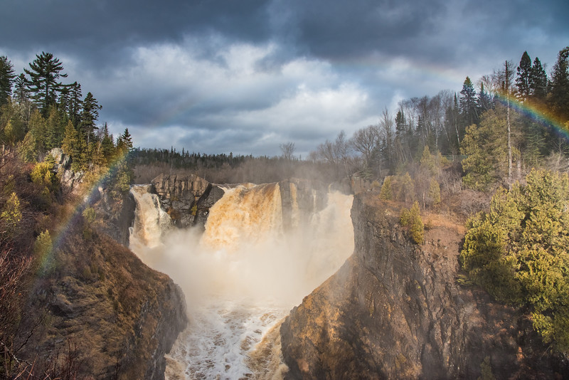 """FRIDAY, NOVEMBER 20, 2015<br /> <br /> PIGEON RIVER 4373<br /> <br /> """"November Rainbow at High Falls""""<br /> <br /> High Falls of the Pigeon River sure looks a lot different than it did a week ago!  In the past week we've received about 4 inches of rain which in turn has raised the Pigeon River water level about 5 feet.  The USGS maintains a monitoring station a couple of miles upstream from High Falls and according to that station the gauge height on the river went from 3 feet to 8 feet!  Yesterday morning I hiked up to the falls to see how it looked after the rain.  I was treated to an awesome view of the falls with high water levels, dark clouds overhead and just enough sunlight poking through the clouds behind me to produce a nice rainbow!<br /> <br /> Camera: Nikon D750<br /> Lens: Nikon 24-120mm f/4<br /> Focal length: 24mm<br /> Shutter speed: 1/800<br /> Aperture: f/11<br /> ISO: 800"""