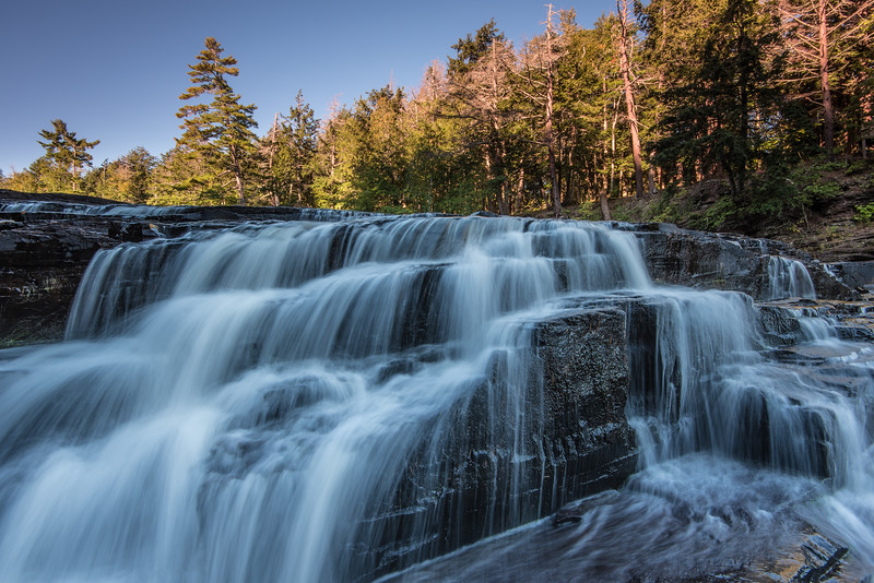 "MONDAY, OCTOBER 5, 2015<br /> <br /> MICHIGAN 2374<br /> <br /> ""First Light at Nawadaha Falls""<br /> <br /> The third waterfall we visited on our trip to the U.P. was Nawadaha Falls in the Porcupine Mountains.  After a chilly night of sleep in the tent we had some breakfast then went for a morning hike along the Presque Isle River.  Even though we had a leisurely start to our morning, the depth of the gorge and the fact that we were on the west side of the Porcupine Mountains meant that the river still did not have any direct light on it.  Which I was grateful for, as I prefer photographing waterfalls in the shade or on cloudy days.  Still, there was quite a bit of contrast in this scene between the very dark foreground and the sunlit background, so I had to use both my 2-stop reverse grad ND filter and my normal 2-stop grad to help balance the exposure.<br /> <br /> Camera: Nikon D750<br /> Lens: Nikon 16-35mm f/4<br /> Focal length: 16mm<br /> Shutter speed: 0.4 seconds<br /> Aperture: f/16<br /> ISO: 100"