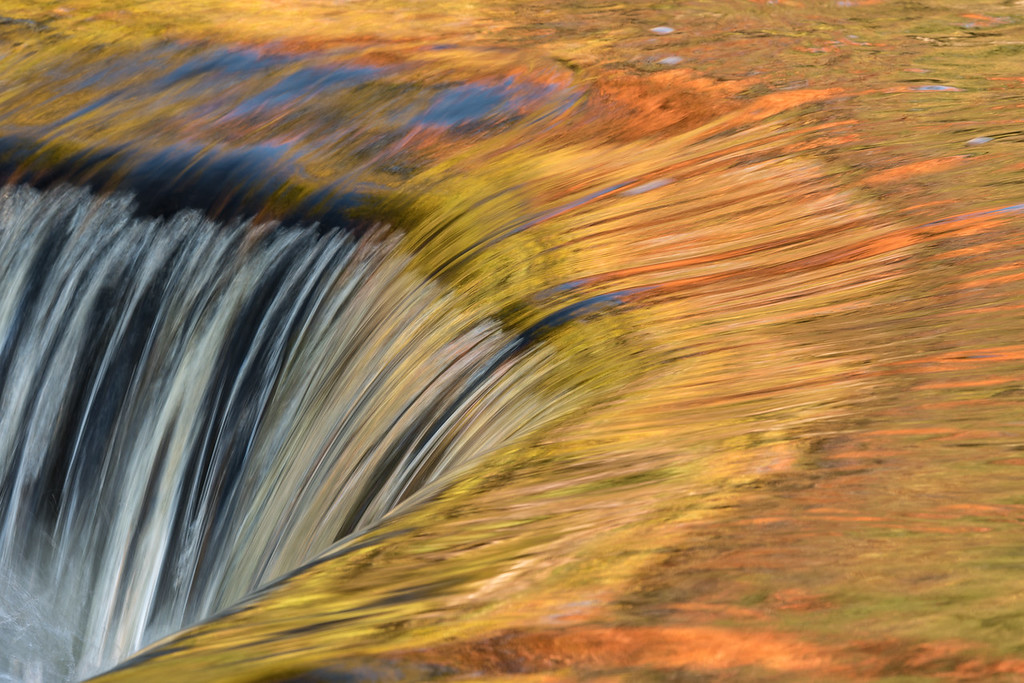 "SATURDAY, OCTOBER 3, 2015<br /> <br /> MICHIGAN 2603<br /> <br /> ""The abstract beauty of Bond Falls""<br /> <br /> There have been a million photos of this particular spot on Bond Falls in the Upper Peninsula of Michigan, but it's one of those things you simply can't resist photographing when you are there.  So, of course I had to make my own interpretation of it :-)  This little section of Bond Falls is a very small drop, only a couple of feet.  But, the way the water reflects the leaf colors of the trees on the opposite side of the river sure is beautiful.<br /> <br /> Camera: Nikon D750<br /> Lens: Tamron SP 150-600mm<br /> Focal length: 280mm<br /> Shutter speed: 1/15<br /> Aperture: f/16<br /> ISO: 100"