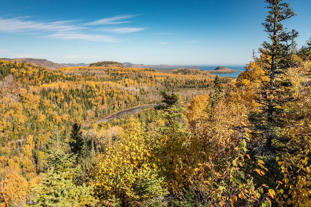 "TUESDAY, OCTOBER 13, 2015<br /> <br /> AUTUMN 3053<br /> <br /> ""Pigeon River Valley Overlook - Middle Falls Trail""<br /> <br /> Looking for a great fall hike?  Check out the Middle Falls Trail at Grand Portage State Park.  It's an adventurous 5 mile round-trip hike that crosses a variety of terrain.  The first half-mile of the trail is paved and brings you to High Falls of the Pigeon River, Minnesota's tallest waterfall.  Backtrack from High Falls just a short distance and you'll see the fork in the trail heading off to Middle Falls.  <br /> <br /> The Middle Falls Trail is a more rugged trail, with lots of rocks and tree roots to step around.  The trail begins climbing almost immediately and before long you are at the top of a ridge that overlooks Lake Superior and the Pigeon River Valley.  This is the high point in elevation on the trail.  You are about 300 to 350 feet higher in elevation than you were at the start of the hike.  The view shown in this photo is the overlook from the top of the ridge, which is a short spur off the main trail.  <br /> <br /> After taking in the overlook view, head back to the main trail and you'll almost immediately descend towards the river. You'll hear the river, but you won't see it until you get to Middle Falls.  Many varieties of trees line the trail including pine, cedar, maple, birch and aspen.  The Middle Falls area is definitely worth the hike, as the trail follows along the river for about a 1/4 mile and provides several nice views of the river.  The real treat is standing right at the top edge of Middle Falls where the river curves right towards you then away as it plunges over the edge and down into a large pool below.  If you haven't done this trail before, I strongly urge you to do so!  It's also a nice hike if you're looking for solitude, as it is one of the lesser-traveled trails along the north shore.<br /> <br /> Camera: Nikon D750<br /> Lens: Nikon 24-120mm f/4<br /> Focal length: 27mm<br /> Shutter speed: 1/640<br /> Aperture: f/11<br /> ISO: 400"