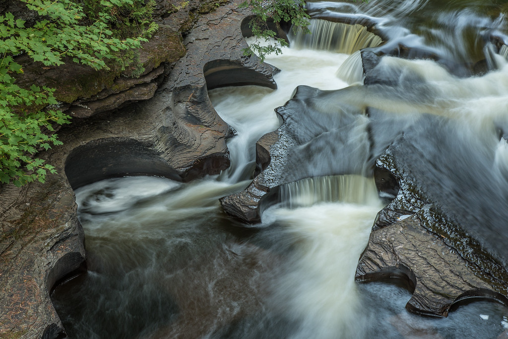 "SUNDAY, OCTOBER 4, 2015<br /> <br /> MICHIGAN 2294<br /> <br /> ""Presque Isle Potholes""<br /> <br /> Jessica and I just returned from a trip to the western upper peninsula of Michigan where we camped at Porcupine Mountains Wilderness State Park and visited several waterfalls.  The first visit of our trip was not far from our campsite and was the famed ""potholes"" near the mouth of the Presque Isle River.  The potholes form where an eddy current continually swirls pebbles and sand grains in a circular path.  Over time, the scouring action of these materials wear away the softer shale, forming the potholes.  The potholes come in all sizes.  We saw several that were only inches across and others that were several feet across.  They certainly are fascinating and one could easily spend a lot of time starting at them as the water swirls around and around.  They are mesmerizing!<br /> <br /> Camera: Nikon D750<br /> Lens: Nikon 24-120mm f/4<br /> Focal length: 75mm<br /> Shutter speed: 1.3 seconds<br /> Aperture: f/16<br /> ISO: 100"
