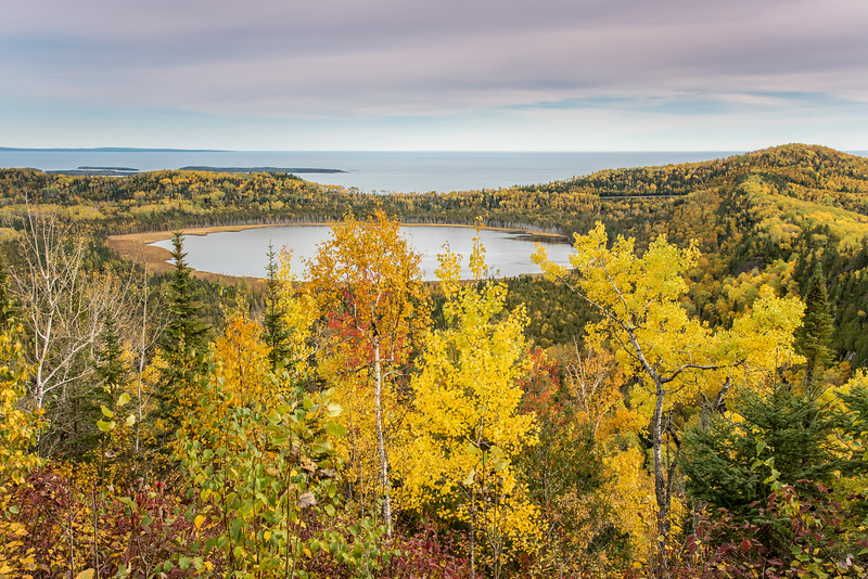 "SATURDAY, OCTOBER 10, 2015<br /> <br /> AUTUMN 2932<br /> <br /> ""Arrowhead Autumn""<br /> <br /> Fall colors near the ""Tip of the Arrowhead"" (the northeastern-most corner of Minnesota) in Grand Portage, MN.  I've been wanting to get to this location to see the fall colors for a few years now.  Finally did it this year!  It's not an easy spot to get to, since there is no established hiking trail.  It's roughly 5 miles round-trip and involves a steep climb up a ridge.  The lake in the foreground is known as Teal Lake, and Lake Superior can be seen in the background.  It's a beautiful spot and we timed it well for the colors.  It was certainly worth the effort to get to this beautiful location!<br /> <br /> Camera: Nikon D750<br /> Lens: Nikon 24-120mm f/4<br /> Focal length: 32mm<br /> Shutter speed: 1/400<br /> Aperture: f/11<br /> ISO: 1000"