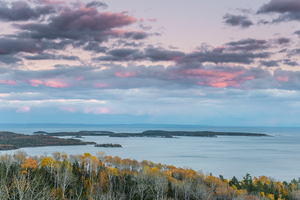 "TUESDAY, OCTOBER 20, 2015<br /> <br /> SUPERIOR FALL 3238<br /> <br /> ""End of Autumn Sunset over the Susie Islands""<br /> <br /> I know it's probably not technically the ""end"" of autumn yet, but I thought it made for a fitting title since this photo shows the last bit of fall leaf color along the shoreline of Wauswaugoning Bay in Grand Portage.  I made this photo on my way home from work a few days ago.  Even though this view is looking more east than west, the clouds were still lighting up nicely from the setting sun.  I thought it made for a nice complement to the remaining color along the shore.  Plus, this view is always spectacular and worth a stop for a photo :-)<br /> <br /> Camera: Nikon D750<br /> Lens: Nikon 24-120mm f/4<br /> Focal length: 62mm<br /> Shutter speed: 1/4<br /> Aperture: f/16<br /> ISO: 200"