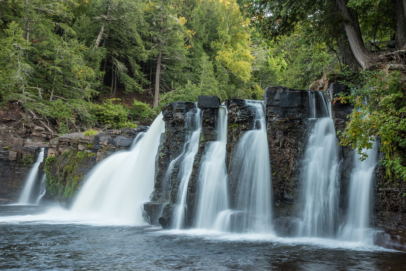 "SUNDAY, OCTOBER 4, 2015<br /> <br /> MICHIGAN 2337<br /> <br /> ""Manabezho Falls""<br /> <br /> The second waterfall we visited on our U.P. Michigan tour was Manabezho Falls of the Presque Isle River in the Porcupine Mountains.  Manabezho is a beautiful waterfall, with several cascades of water tumbling over the cliff face.  With a drop of roughly 25 feet it is the largest waterfall on the Presque Isle River.  I found it to be an immensely fun waterfall to photograph :-)<br /> <br /> Camera: Nikon D750<br /> Lens: Nikon 24-120mm f/4<br /> Focal length: 55mm<br /> Shutter speed: 0.5 seconds<br /> Aperture: f/22<br /> ISO: 200"