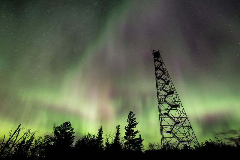 "SUNDAY, SEPTEMBER 20, 2015<br /> <br /> AURORA 0528<br /> <br /> ""Fire Tower Light Show""<br /> <br /> Just when you think a promising aurora forecast isn't going to pan out, it goes and surprises you!  That's exactly what happened last night.  According to space weather forecasters, as sunset approached last night we were entering into a watch period for aurora storms.  I was keeping an eye on the websites that track and predict aurora activity and by 11:30 PM there really wasn't any sign of anything good happening, so I decided to go to bed.  Luckily, I woke up a little after 3 PM to go to the bathroom and decided to check the websites again.  As luck would have it, the aurora activity was picking up so I decided to head out and try to make some photographs.  As I was driving up the hill away from Lake Superior I could see a large ribbon of lights developing in the northern sky.  The ribbon was bright but low in the sky so I decided to head to the top of a hill where there is an old fire tower.  I figured the elevated vantage point would give me a good view of the lights.  Well, it certainly worked!  By the time I got to the location the lights had expanded to fill almost half of the sky.  I spent the next two hours on top of the hill photographing a very good display of the northern lights!<br /> <br /> Camera: Nikon D750<br /> Lens: Nikon 14-24mm f/2.8<br /> Focal length: 14mm<br /> Shutter speed: 15 seconds<br /> Aperture: f/2.8<br /> ISO: 1600"