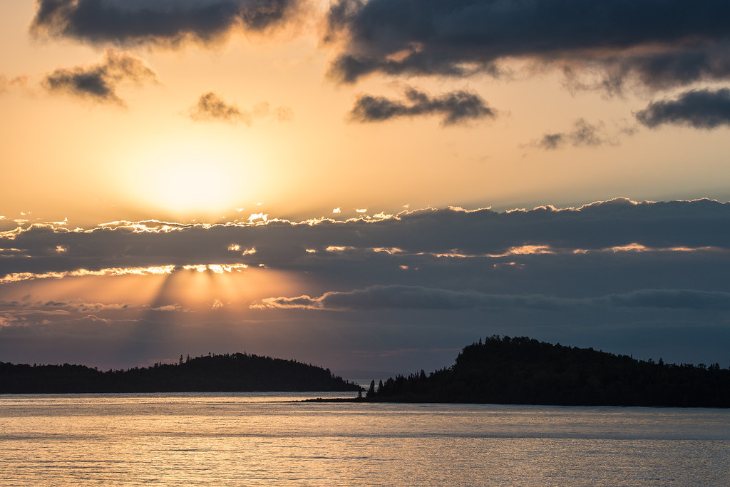 """WEDNESDAY, SEPTEMBER 23, 2015<br /> <br /> SUPERIOR FALL 0559<br /> <br /> """"Good Morning Grand Portage!""""<br /> <br /> Sunrise over Lake Superior, Hat Point and Pete's Island in Grand Portage.  Isle Royale National Park is also visible on the horizon in between in the point and the island.  What a gorgeous way to start the day!<br /> <br /> Camera: Nikon D750<br /> Lens: Tamron SP 150-600mm<br /> Focal length: 150mm<br /> Shutter speed: 1/800<br /> Aperture: f/11<br /> ISO: 400"""