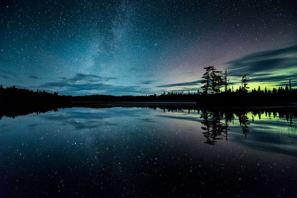 "THURSDAY, SEPTEMBER 10, 2015<br /> <br /> MILKY WAY 9797<br /> <br /> ""Stellar Sky in the Land of 10,000 Lakes""<br /> <br /> A star-filled night complemented by a hint of Aurora Borealis (northern lights) in the land of 10,000 lakes.  Taken a few nights ago in Grand Portage State Forest, northeast Minnesota.  I've always wanted to capture an image where there seemed to be just as many stars reflected in the water as there were in the sky, but until now have never had a calm enough night when I've been out.  I've captured star reflections in lakes before, but never so many as on this night.  The air was completely still and the surface of the lake shimmered with reflected starlight.  It was one of the most beautiful things I've ever seen.  Thankfully it's early September and the nights are cooler with virtually no bugs.  If this had been earlier in the summer I would have been eaten alive by mosquitoes on a night such as this!<br /> <br /> Camera: Nikon D750<br /> Lens: Nikon 14-24mm f/2.8<br /> Focal length: 14mm<br /> Shutter speed: 30 seconds<br /> Aperture: f/2.8<br /> ISO: 6400"
