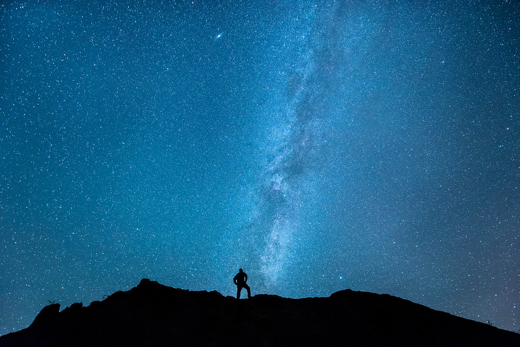 """MONDAY, SEPTEMBER 14, 2015<br /> <br /> MILKY WAY 0055<br /> <br /> """"Alone with the Milky Way""""<br /> <br /> I went out last night with the intention of photographing the Milky Way over a new lakeside location that I haven't tried yet.  I had to alter my plan, however, as the wind was much too strong to get the reflections I was hoping for in the water.  I wasn't sure where to go after that, so I just drove around until I got an idea to try a local gravel pit. I wanted to see if there were any interesting trees along the edge of the pit to compose as a silhouette against the sky.  What I found instead was a very nice gravel pile that lined up perfectly with the Milky Way.  I decided to set my camera to take one exposure after another then walk to the top of the gravel pile to pose in the shot.  What you see here is what I ended up with.  I think it looks like a photo that might have been made in the Badlands or in Utah rather than northern Minnesota.  Kind of fun, I think :-)<br /> <br /> Camera: Nikon D750<br /> Lens: Nikon 14-24mm f/2.8<br /> Focal length: 14mm<br /> Shutter speed: 30 seconds<br /> Aperture: f/2.8<br /> ISO: 6400"""