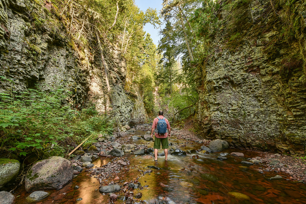 """WEDNESDAY, SEPTEMBER 16, 2015<br /> <br /> RIVERS 0281<br /> <br /> """"Hiking the Kadunce River""""<br /> <br /> Here's a """"self portrait"""" that I did while hiking the Kadunce River yesterday.  I wanted to put myself in the picture mostly to provide a sense of scale for the size of the gorge.  When you are hiking up this river there are times where the canyon walls feel like they are towering above you.  Without a person in the photo it's hard to get that sense of scale.  I love walking up shallow rivers, especially on a warm September day.  It's definitely one of the best ways to enjoy a day on the north shore of Lake Superior!<br /> <br /> Camera: Nikon D750<br /> Lens: Nikon 14-24mm f/2.8<br /> Focal length: 14mm<br /> Shutter speed: 1/5<br /> Aperture: f/16<br /> ISO: 100"""
