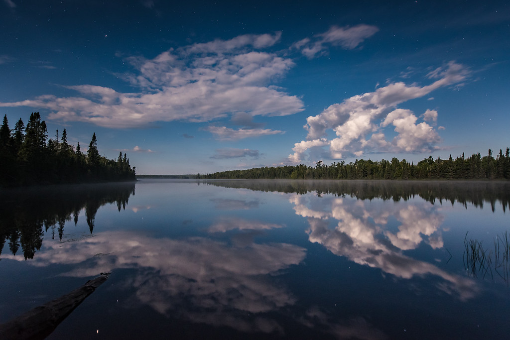 "FRIDAY, AUGUST 19, 2016<br /> <br /> MOONLIGHT 9606<br /> <br /> ""Moonlit Clouds on Cascade Lake""<br /> <br /> A beautiful moonlit evening on the shoreline of Cascade Lake in the Superior National Forest.  I had spent the afternoon hiking up to Carlton Peak near Tofte and riding the singletrack mountain bike trails at Britton Peak.  I finished my bike ride right at sunset and decided to take the backroads home. I'm glad I did because I was treated to some really nice views along the way!  In this photo the moon was rising behind me and nicely illuminating these clouds to the west. <br /> <br /> Camera: Nikon D750<br /> Lens: Nikon 14-24mm f/2.8<br /> Focal length: 19mm<br /> Shutter speed:  10 seconds<br /> Aperture: f/2.8<br /> ISO: 1600"