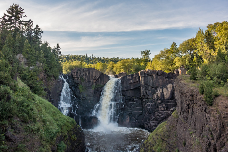 "SATURDAY, AUGUST 27, 2016<br /> <br /> PIGEON RIVER 02319<br /> <br /> ""August Evening at High Falls""<br /> <br /> Last night after work I hiked the Middle Falls Trail in Grand Portage State Park, a rugged hike of almost 5 miles that covers a really nice mix of terrain.  On the return portion of the hike I decided to take the short spur up to High Falls, since I hadn't seen or photographed that waterfall in a while.  The water level is definitely getting on the low side as we haven't had much rainfall lately.  The ridge behind the falls was illuminated from the light of the setting sun.  The evening light combined with some nice clouds made for an interesting photograph.<br /> <br /> Camera: Sony DSC-RX100M3<br /> Focal length: 34mm<br /> Shutter speed: 1/800<br /> Aperture: f/3.5<br /> ISO: 100"