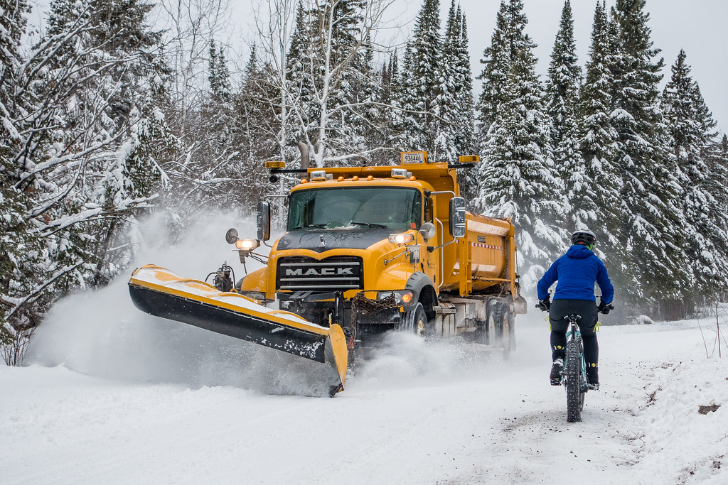 "TUESDAY, DECEMBER 20, 2016<br /> <br /> BIKING 04526<br /> <br /> ""Snow Ride - Meeting the Plow""<br /> <br /> Today we rode our fat bikes on Old Highway 61 in Grand Portage, MN to the old border crossing and back.  It was an awesome day, with a temperature right around 32 degrees.  Super comfortable for riding!  Along the way we saw the county plow coming and I quickly pulled out the camera to make this photo as the plow met with Jessica.  I thought it made for a cool shot!<br /> <br /> Camera: Sony DSC-RX100M3<br /> Focal length: 67mm<br /> Shutter speed: 1/500<br /> Aperture: f/4<br /> ISO: 200"