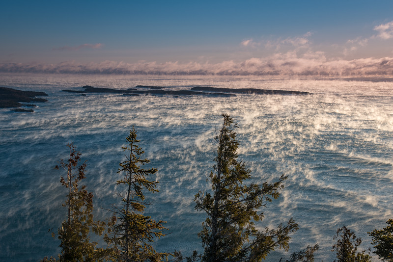 "FRIDAY, DECEMBER 16, 2016<br /> <br /> SUPERIOR WINTER 1841<br /> <br /> ""Lake Superior Sea Smoke from the summit of Mt. Josephine""<br /> <br /> Yesterday morning I got up early to make the trek up Mt. Josephine to photograph the sea smoke on Lake Superior.  I knew that the high vantage point (the summit is 700 feet in elevation above the lake) would make for excellent viewing of one of Lake Superior's most fascinating phenomenon.  I love the winter and sea smoke is one of the reasons why.  As cold arctic air moves in and hits the (comparatively) warm water of Lake Superior, it makes steam that rises off the surface of the lake.  Commonly referred to as sea smoke, it makes for a fascinating photographic subject.  <br /> <br /> All night long the wind blew like crazy.  I was hoping it would die down by morning as I really wanted to hike up the mountain but didn't want to do it in the crazy wind.  Thankfully, around 5:00 A.M. the wind did let up considerably.  I crawled out of bed at 6:30 and bundled up for the trek up the mountain.  On the short drive to the trailhead my car was indicating that the temperature outside was minus 5 degrees Fahrenheit.  There was still some wind, but it wasn't bad.  I had a mile of hiking to do with a 700 foot gain in elevation.  The trick was to move slow and steady.  I didn't want to get too warm and sweat too much on the way up, because then I would be freezing while I stood on the summit making photographs.  <br /> <br /> About halfway up the mountain I started get back into the wind.  It had been relatively calm down at the start of the trail but as I gained elevation the wind picked up again.  By the time I got to the summit it was howling pretty good.  Luckily, the wind was mostly at my back as I stood making photographs of the lake.  I spent about an hour on the summit making photos and timelapse sequences of the sea smoke as the wind pushed it out across the surface of the lake.  I came home with a lot of cool images and enough timelapse sequences to make a nice little video compilation, which I will be sharing later today.  I had a little bit of a chill the rest of the day after this outing, so going to the hot tub last night at the community center sure felt good!<br /> <br /> <br /> Camera: Nikon D750<br /> Lens: Nikon 24-120mm f/4<br /> Focal length: 50mm<br /> Shutter speed: 1/60<br /> Aperture: f/11<br /> ISO: 100"