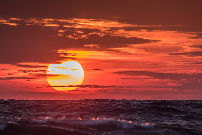 """THURSDAY, JANUARY 7, 2016<br /> <br /> SUPERIOR WINTER 6466<br /> <br /> """"Sunset on Superior""""<br /> <br /> We sure have had some nice sunsets already this year!  This one was taken the other day from the shoreline in Grand Marais, MN.  It was a VERY windy day, as you can see from the waves along the bottom of the photo.  The sunset was one of the most surreal that I've ever witnessed over Lake Superior (and I've seen a LOT of them over the years!).  The waves, the clouds, the colors, the sun... it was all simply amazing!<br /> <br /> Camera: Nikon D750<br /> Lens: Tamron SP 150-600mm<br /> Focal length: 600mm<br /> Shutter speed: 1/400<br /> Aperture: f/11<br /> ISO: 200"""