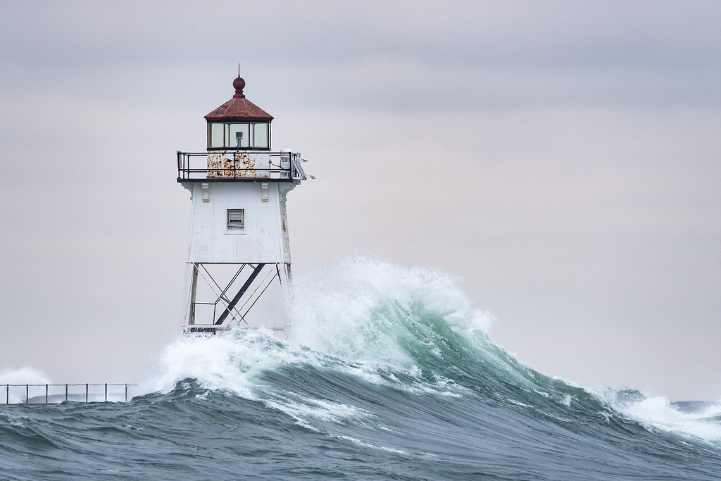 "FRIDAY, JANUARY 8, 2016<br /> <br /> SUPERIOR WAVES 6229<br /> <br /> ""Crash Course""<br /> <br /> This wave appears to be on a crash course with the Grand Marais lighthouse!  If I remember correctly the wave actually passed just off the end of the break wall without actually hitting the lighthouse. The compressed point of view from the telephoto lens, however, makes it appear as though the wave is going to collide head-on with the lighthouse.  Any way you look at it, it sure is a big wave!<br /> <br /> Camera: Nikon D750<br /> Lens: Tamron SP 150-600mm<br /> Focal length: 460mm<br /> Shutter speed: 1/1000<br /> Aperture: f/10<br /> ISO: 1600"