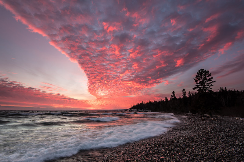 "WEDNESDAY, JANUARY 6, 2016<br /> <br /> SUPERIOR WINTER 6507<br /> <br /> ""January Sunset - Grand Marais, Minnesota""<br /> <br /> After a fun-filled day of wave watching on the Lake Superior shoreline, we were treated to one of the best sunsets I've ever seen.  The clouds lit up like fire and stayed that way for a long time.  The shape of the clouds was really interesting too.  The awesome sky combined with the rough waters of the lake made for quite the scene. I can't imagine the day could have ended any better than this!<br /> <br /> Camera: Nikon D750<br /> Lens: Nikon 16-35mm f/4<br /> Focal length: 16mm<br /> Shutter speed: 0.4 seconds<br /> Aperture: f/11<br /> ISO: 200"