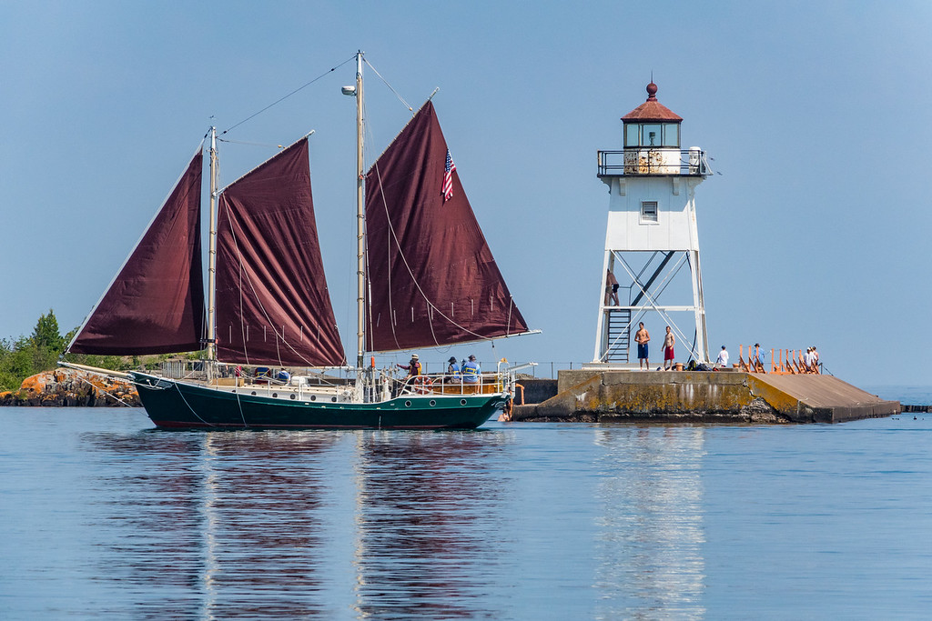 "THURSDAY, JULY 21, 2016<br /> <br /> GRAND MARAIS 00397<br /> <br /> ""A Beautiful Day in Grand Marais!""<br /> <br /> Boy, it sure was a nice day yesterday!  As luck would have it I found myself in Grand Marais with a few hours to kill so for part of that time I sat on the shoreline of the harbor and watched the summer activity.  Boats and kayaks came and went, as did a large variety of people over at the lighthouse.  When I first sat down along the shoreline the sailing schooner Hjordis was just setting out onto the lake.  I made some photos of it as it passed the lighthouse but I wasn't really happy with the way they turned out.  So, I decided to wait for it to come back into the harbor to try again.  <br /> <br /> Over an hour later the boat finally returned and I got a shot that I'm much happier with.  As the boat was passing by the lighthouse a group of kids was taking turns jumping off the breakwall into the lake.  They paused from their swim antics to watch as the Hjordis sailed past.  It was the kind of summer day that everyone dreams about and there certainly were a lot of people out taking advantage of it!<br /> <br /> Camera: Sony DSC-RX10M3<br /> Focal length: 320mm<br /> Shutter speed: 1/1250<br /> Aperture: f/8<br /> ISO: 400"