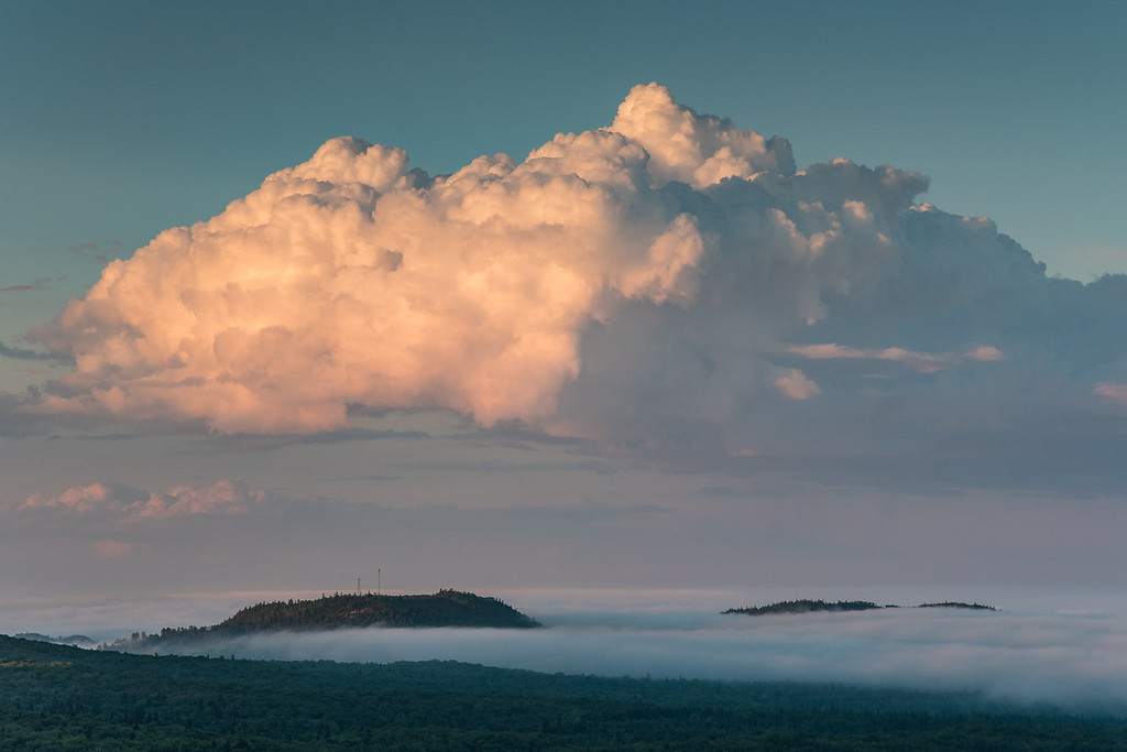 "SUNDAY, JULY 10, 2016<br /> <br /> CLOUDS 8881<br /> <br /> ""Sunset Cloud over Mt. Maude""<br /> <br /> The other day we had lots of fog over the Lake Superior shoreline.  Inland, however, it had been sunny and hot all day.  As sunset approached I decided to take a drive inland to see if I could find the edge of the fog.  Sure enough, the fog only extended a couple of miles away from the lake.  I went up to my favorite fire tower to view the fog from an elevated vantage point.  It's always a bit surreal to be above the fog looking down on it.  Such conditions make for some of the most unique photographs. Such as this photo of a large cloud illuminated by the setting sun as it hovered directly over the towers on Mt. Maude.  I sure am glad I decided to make the trek up to this location!<br /> <br /> Camera: Nikon D750<br /> Lens: Nikon 24-120mm f/4<br /> Focal length: 105mm<br /> Shutter speed: 1/160<br /> Aperture: f/11<br /> ISO: 400"